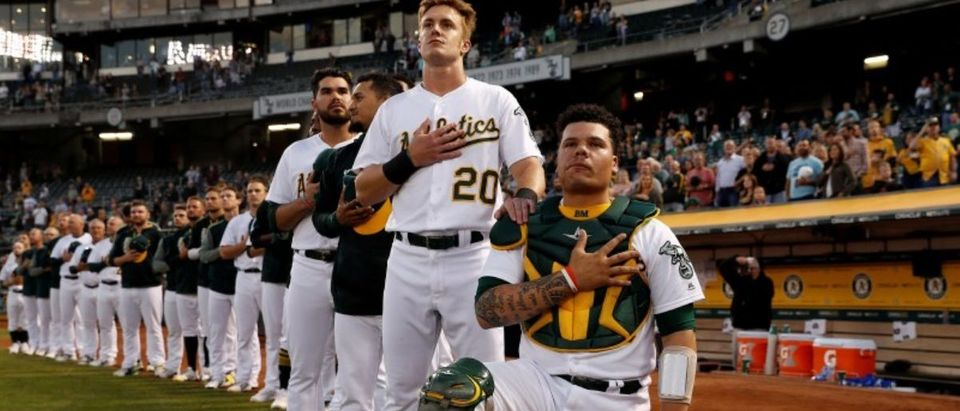 Bruce Maxwell of the Oakland Athletics kneels during the singing of the National Anthem before game againt Seattle Mariners in Oakland, California