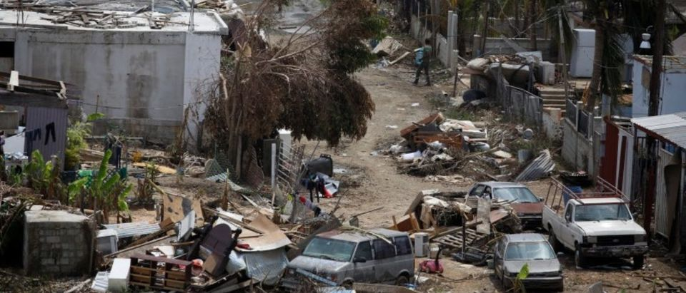 A man carrying a water container walks next to damaged houses after the area was hit by Hurricane Maria in Canovanas