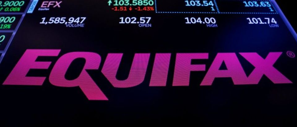The logo and trading information for Credit reporting company Equifax Inc. are displayed on a screen on the floor of the NYSE in New York