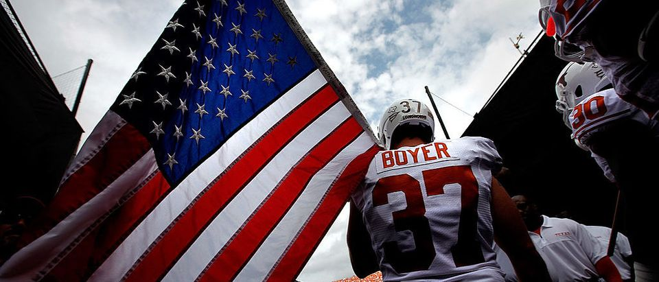Nate Boyer during a game in college playing for Texas, carrying the flag onto the field. (Photo by Tom Pennington/Getty Images)