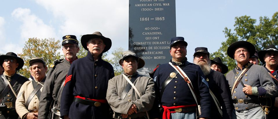 Re-enactors pose for a group photo in front of a monument honouring Canadians who fought in the U.S. Civil War during a dedication ceremony at Ault Park in Long Sault