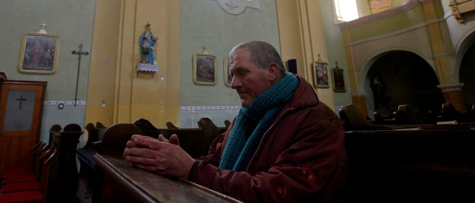 A man prays in a Catholic church in the eastern Hungarian village of Alattyan January 18, 2007. The family of French presidential candidate Nicolas Sarkozy owned estates in Alattyan and the father of Sarkozy, Pal Sarkozy, spent summers in the 1930s and 1940s in the village. Picture taken January 18, 2007. REUTERS/Laszlo Balogh (HUNGARY) - GM1DUKPGLWAA
