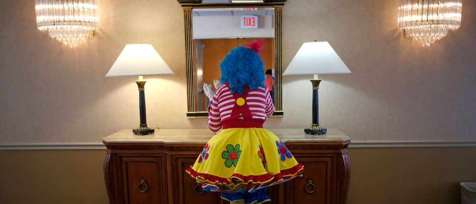 A clown checks her makeup in a hotel hallway mirror before competing at the World Clown Association's annual convention in Northbrook (Reuters)