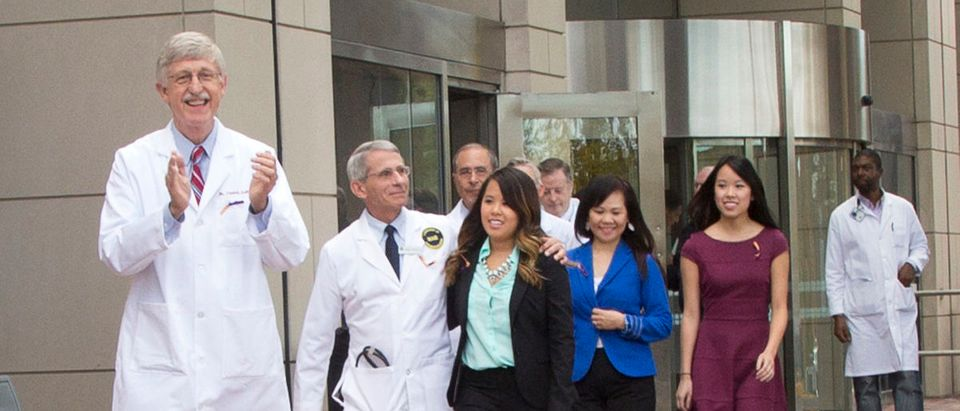 NIH Director Dr. Francis Collins, NIAID Director Dr. Anthony Fauci and NIH Clinical Center Director Dr. John Gallin exit the NIH Clinical Center in Bethesda, Maryland with recently discharged Ebola patient Nina Pham