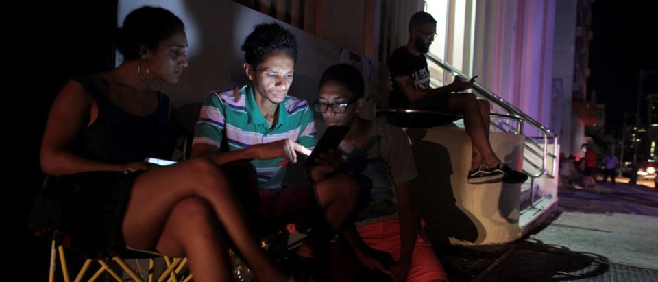 People use their cellphones on the street during a blackout after the area was hit by Hurricane Maria in San Juan