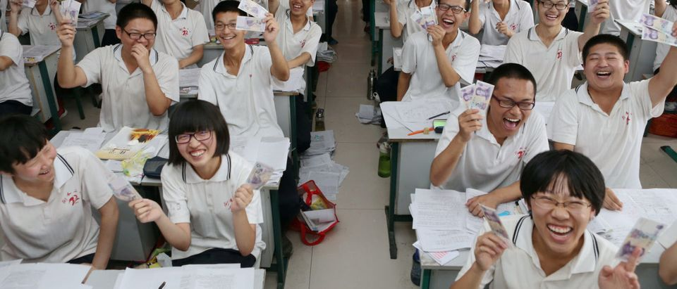 """Students hold and present 5 yuan banknotes as they pose to camera with their teacher at a classroom ahead of China's annual national college entrance exam or """"gaokao"""" in Hengshui"""