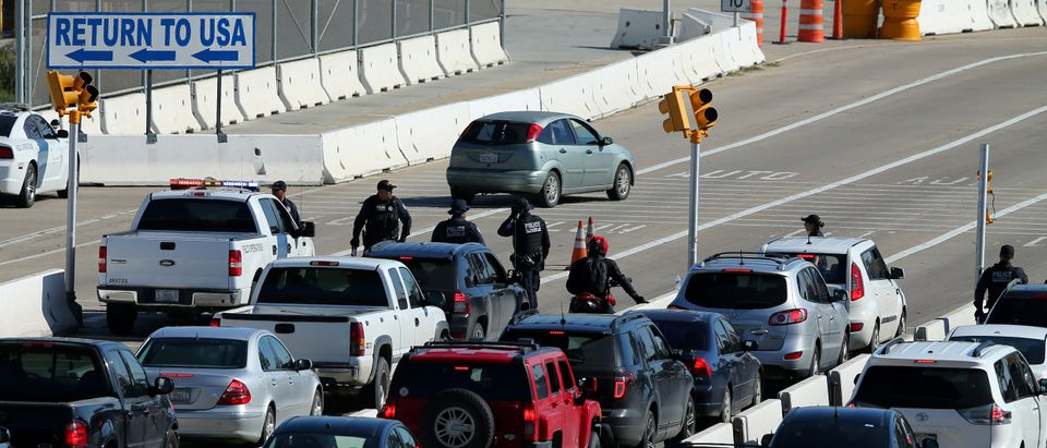 U.S. Customs and Border Patrol agents stop traffic heading into Mexico to check vehicles leaving the country in San Ysidro, California