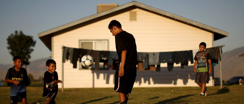 Children play soccer at a migrant farm labour housing center in Bakersfield