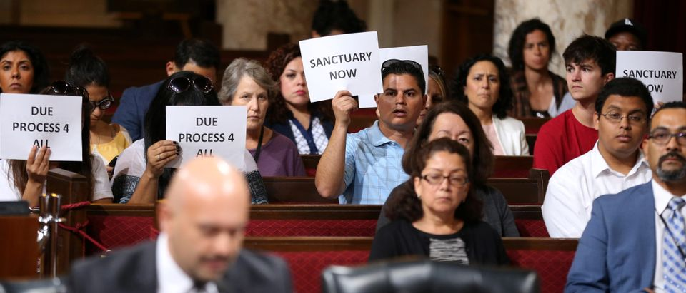 Immigrant supporters protest duirng the Los Angeles City Council ad hoc committee on immigration meeting to discuss the city's response to threats by the Trump administration to cut funding from Los Angeles and other jurisdictions which federal officials s