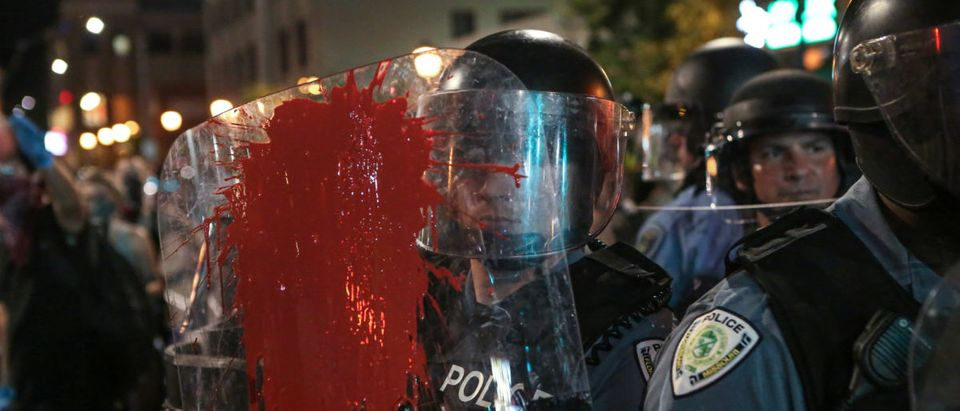 Red paint is splattered on the shield of a policeman during the second night of demonstrations after a not guilty verdict in the murder trial of former St. Louis police officer Jason Stockley, charged with the 2011 shooting of Anthony Lamar Smith, who was black, in St. Louis, Missouri, U.S., September 16, 2017. Photo taken September 16, 2017. REUTERS/Lawrence Bryant