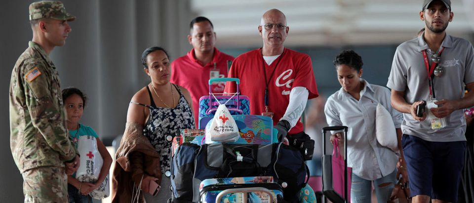 People push a luggage trolley after arriving along with other refugees onboard the Royal Caribbean's Majesty of the Seas cruise ship from St. Thomas, U.S. Virgin Islands, in San Juan