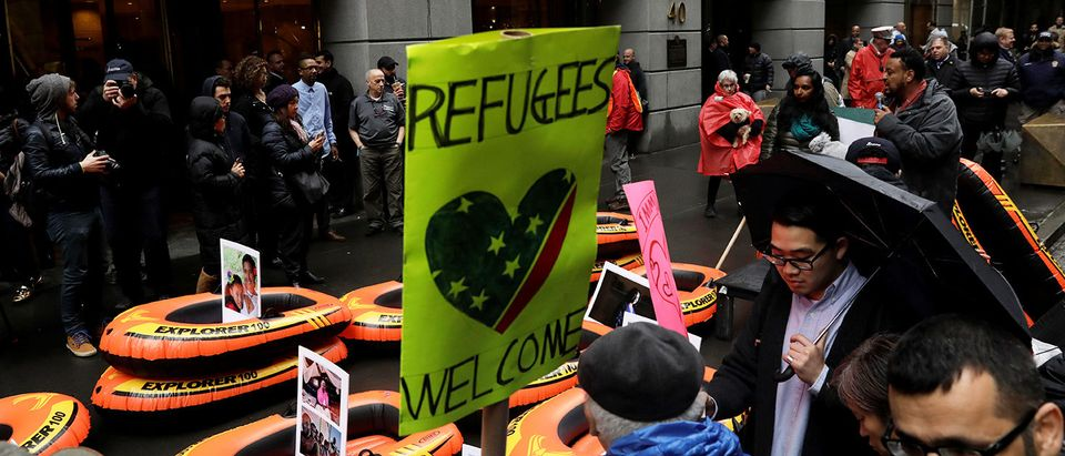 Protesters gather outside the Trump Building at 40 Wall St. to take action against America's refugee ban in New York