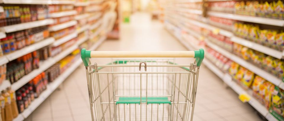 Supermarket aisle with empty red shopping cart with customer defocus background Makistock (Shutterstock)