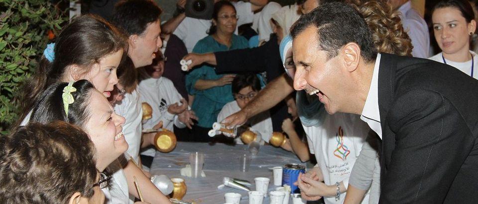 Syrian President Bashar Assad (R) shares