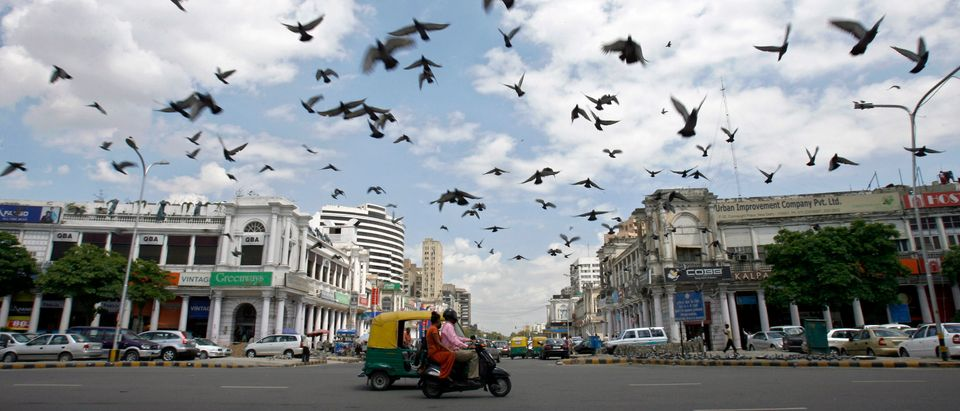 Pigeons fly as clouds gather over New Delhi's Connaught Place