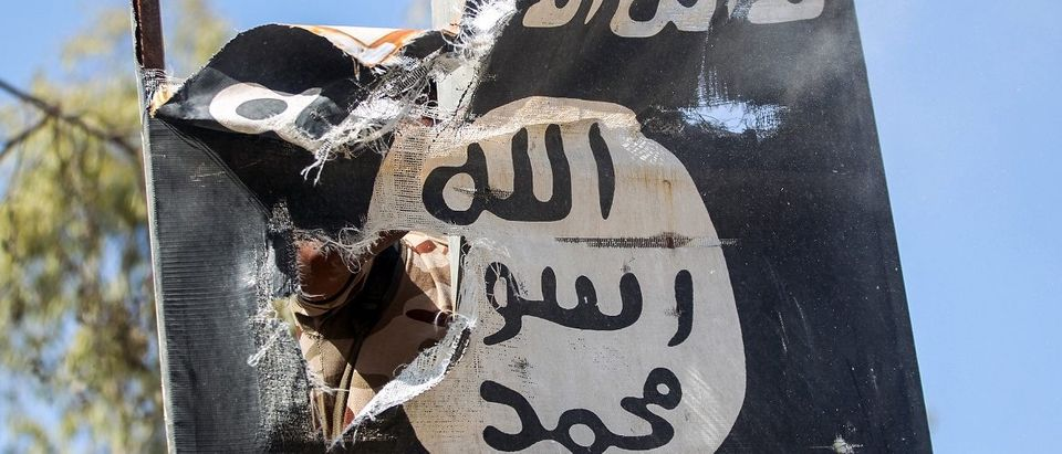 A member of Hashed Al-Shaabi (Popular Mobilization units) removes a sign on a lamp post bearing the logo of the Islamic State (IS) group as Iraqi forces advance inside the town of Tal Afar, west of Mosul, after the Iraqi government announced the launch of the operation to retake it from IS control, on August 26, 2017. Ahmad al-Rubaye/AFP/Getty Images.