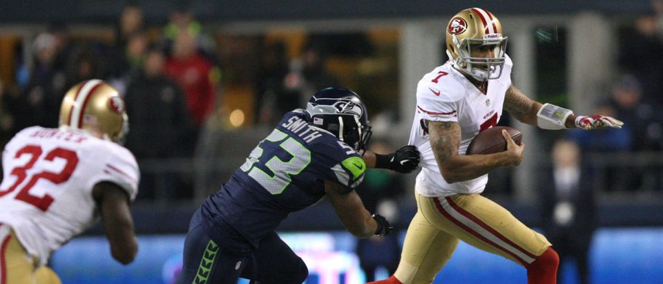 San Francisco 49ers quarterback Colin Kaepernick (R) is chased by Seattle Seahawks Malcom Smith (C) during the fourth quarter in the NFL's NFC Championship football game in Seattle, January 19, 2014. REUTERS/David Ryder