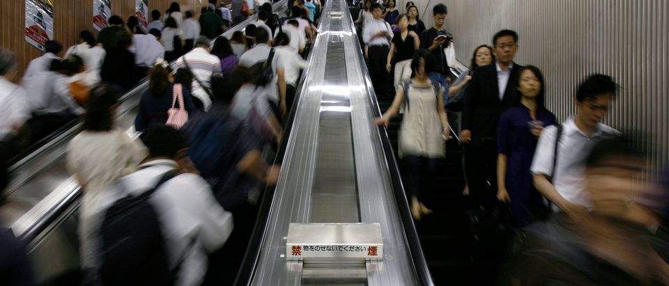 Commuters ride escalators at a subway station in Tokyo