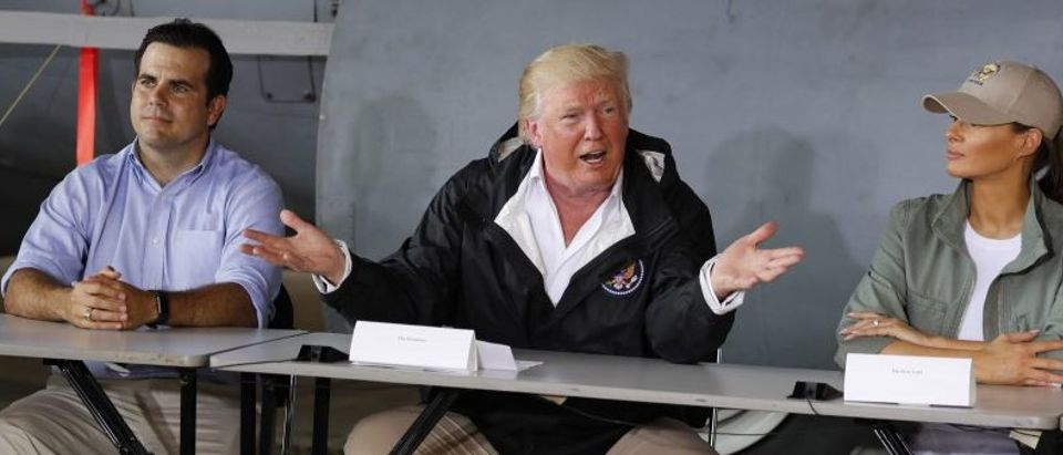 U.S. President Donald Trump sits between Puerto Rico Governor Ricardo Rossello and first lady Melania Trump, as he receives a briefing on hurricane damage at Muniz Air National Guard Base in Carolina, Puerto Rico, U.S., October 3, 2017. REUTERS/Jonathan Ernst