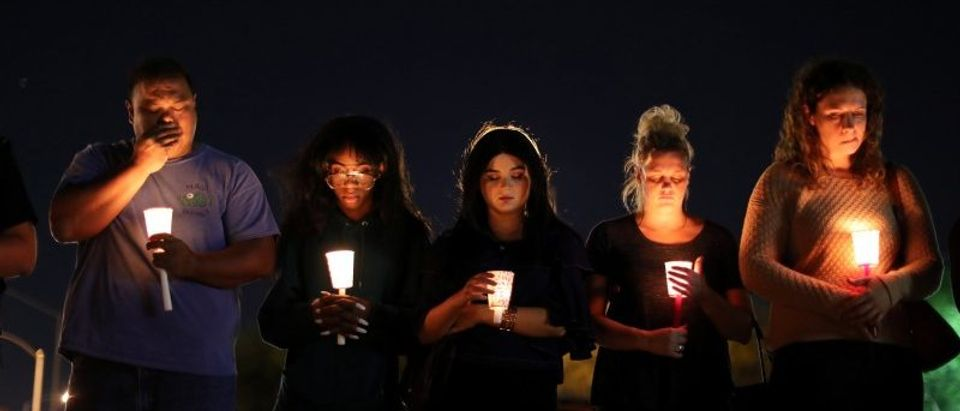 People pray during a candlelight vigil for victims of the Route 91 music festival mass shooting next to the Mandalay Bay Resort and Casino in Las Vegas