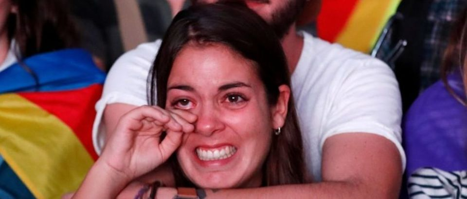 Woman reacts while watching Catalonian regional parliament session on giant screen in Barcelona