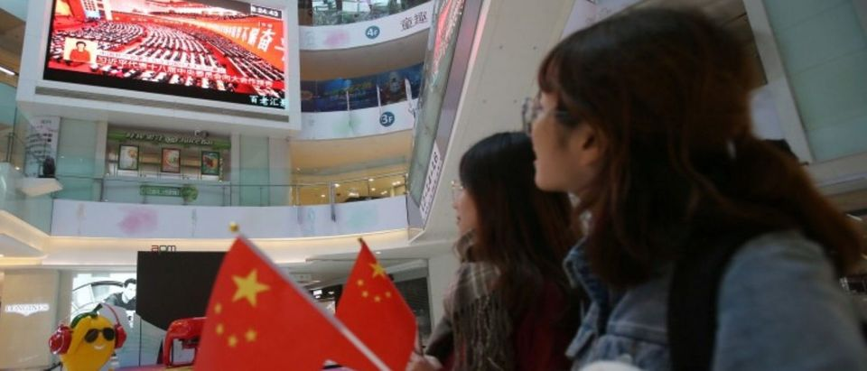 People watch a broadcast of Chinese President Xi Jinping delivering his speech during the opening of the 19th National Congress of the Communist Party of China, at a shopping mall in Beijing