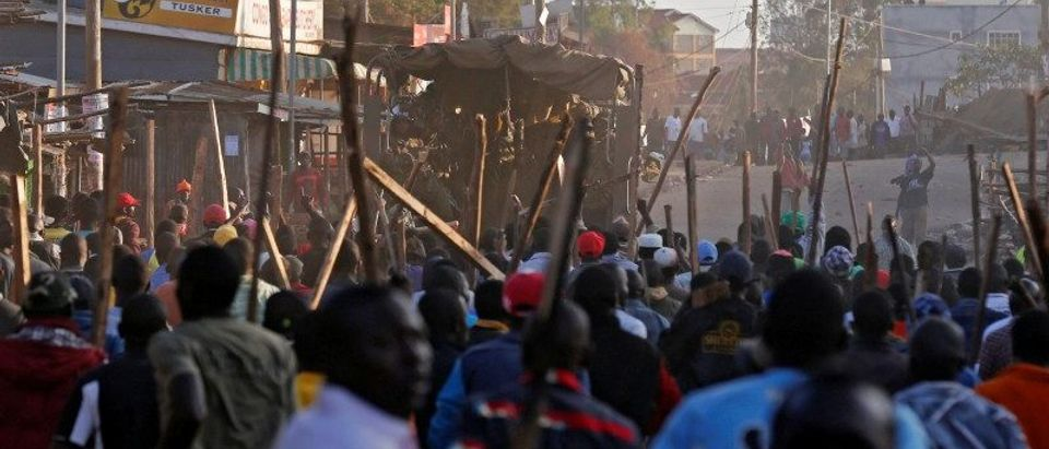 Rioters carry sticks as they walk near a police vehicle in Kawangware slums in Nairobi