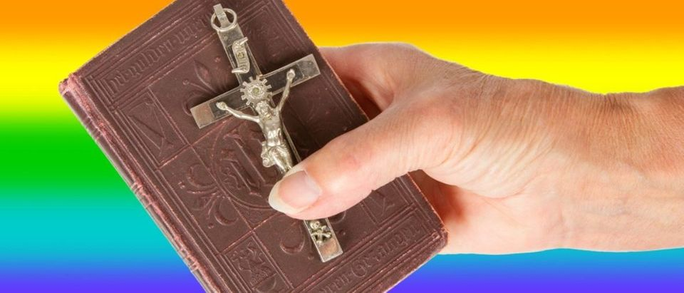 Here is Bible held in front of an LGBT flag. (shutterstock/MyImages - Micha)