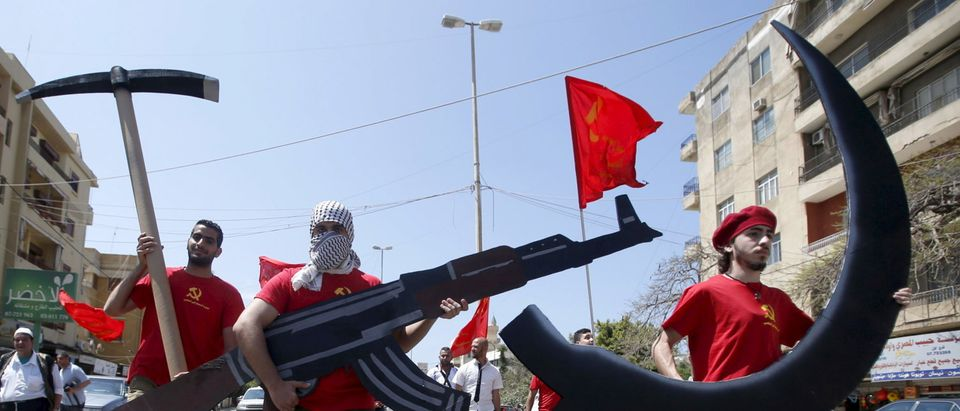 Protestors attend a march organised by Democratic People's Party members, part of the Lebanese Communist party, carrying a sickle, hammer and kalashnikov cut outs to mark Labour Day in Sidon, south Lebanon