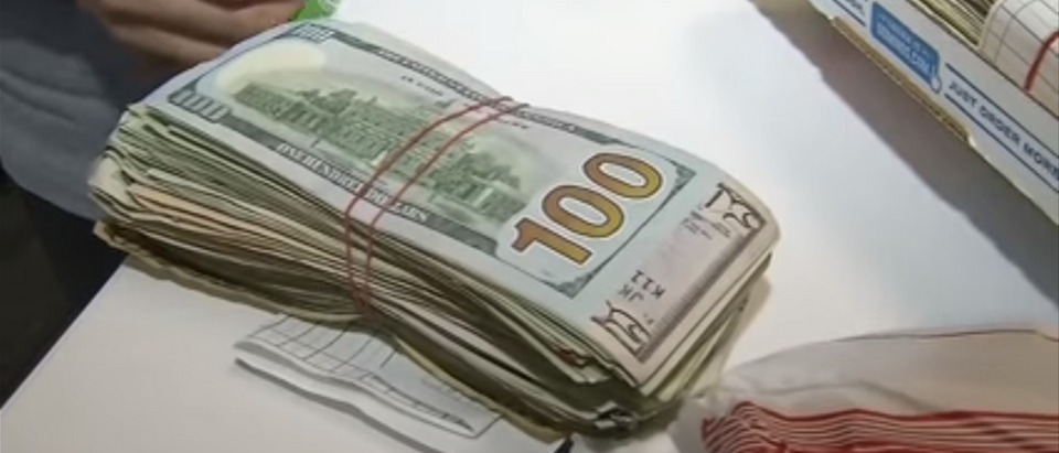 A woman found this stack of dollar bills in a pizza box. (Photo Credit: YouTube/NBC4 WCMH-TV Columbus)