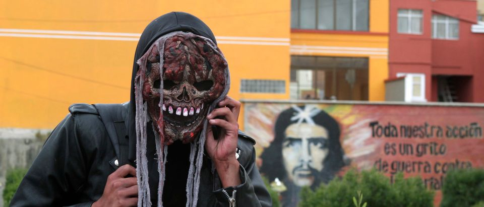 A man wearing a costume talks on a mobile phone in front of a picture of Argentine guerrilla leader Guevara during an annual Halloween celebration in La Paz