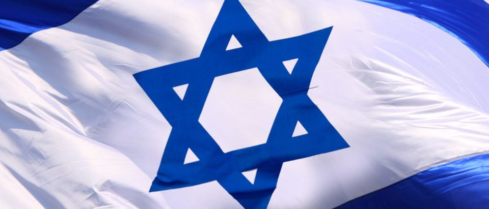 The Israeli flag waves in the wind. (Shutterstock/omnimoney)
