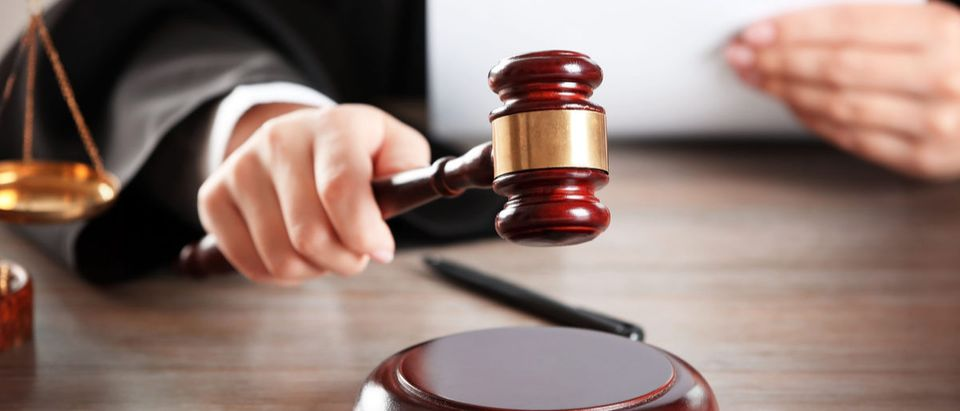 Judge hitting gavel with paper at wooden table closeup Africa Studio (Shutterstock)