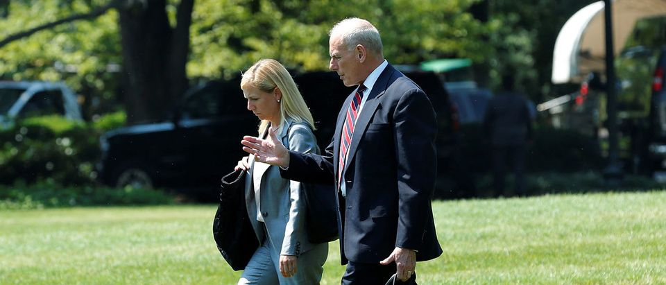 White House Chief of Staff John Kelly (R) walks on the South Lawn