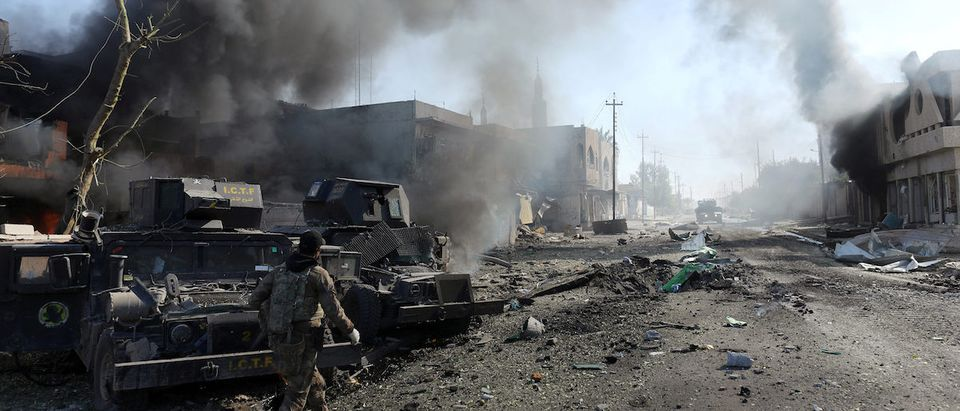 An Iraqi special forces soldier walks in front of humvees destroyed by an Islamic State suicide car bomb attack during clashes in Mosul