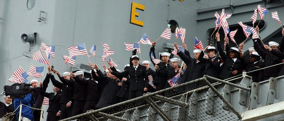 Sailors aboard the USS Roosevelt wave to loved ones as the aircraft carrier returns to port at the U..