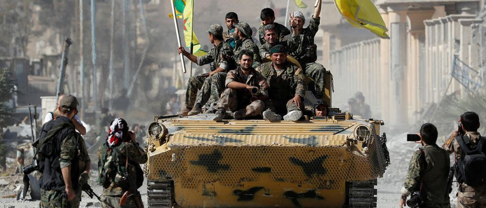 Fighters of Syrian Democratic Forces ride atop of an armoured vehicle after Raqqa was liberated from the Islamic State militants, in Raqqa
