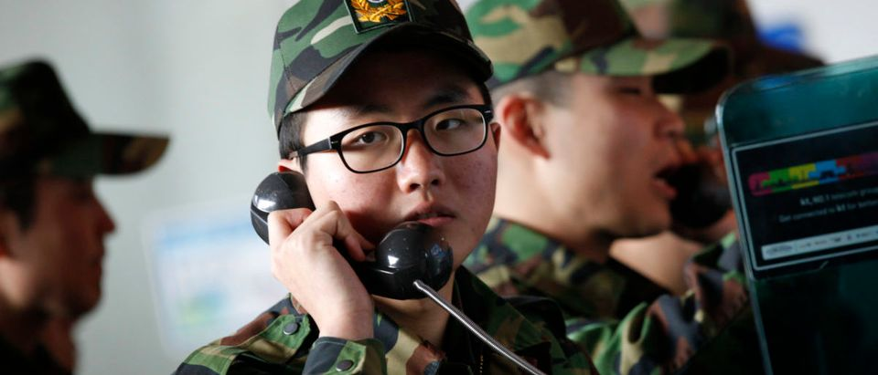 South Korean soldiers who are going to return to their units, use public phones at Seoul railroad station in Seoul