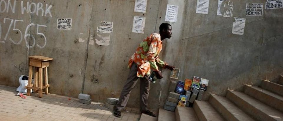 FILE PHOTO: A man arranges books for sale on a pedestrian bridge where posters advertising jobs are pasted in Lagos