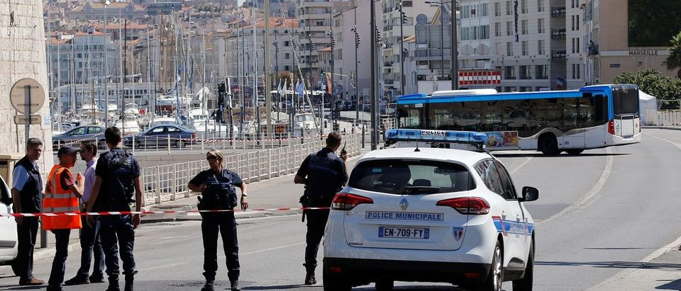 French police block the street after one person was killed and another injured after a vehicle crashed into two bus shelters