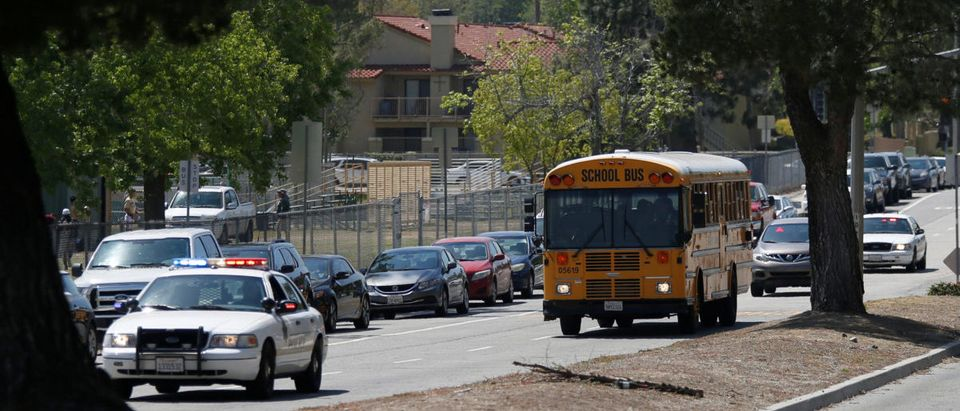 Police cars escort students in a bus after a shooting at North Park Elementary School, to be reunited with their parents in San Bernardino, California, U.S. April 10, 2017. REUTERS/Mario Anzuoni