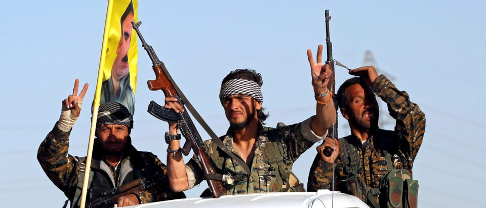 Fighters of Syrian Democratic Forces make the V-sign as their convoy passes in Ain Issa