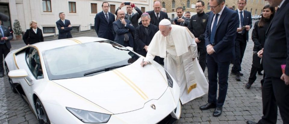 Pope Francis signs a Lamborghini Huracan prior to his Wednesday general audience in Saint Peter's square at the Vatican, November 15, 2017. Osservatore Romano/Handout via REUTERS