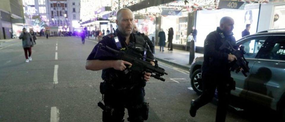 Armed police run along Oxford Street, London