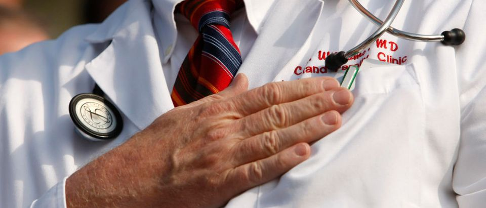 "A doctor puts his hand over his chest during a ""House call"" rally against proposed healthcare reform legislation at the Capitol in Washington November 5, 2009. (Photo: REUTERS/Kevin Lamarque)"