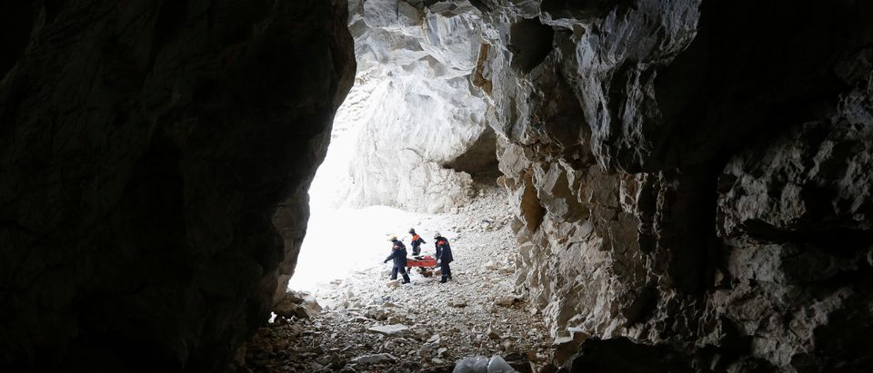 """Members of the """"Spasatel"""" (Rescuer) state regional search and rescue service group carry a full-size wooden dummy inside a karstic cave during a training session dedicated to evacuation under the conditions of rock climbing on the bank of the frozen Biryusa Bay of Yenisei River near Krasnoyarsk, Siberia, March 3, 2015. REUTERS/Ilya Naymushin"""