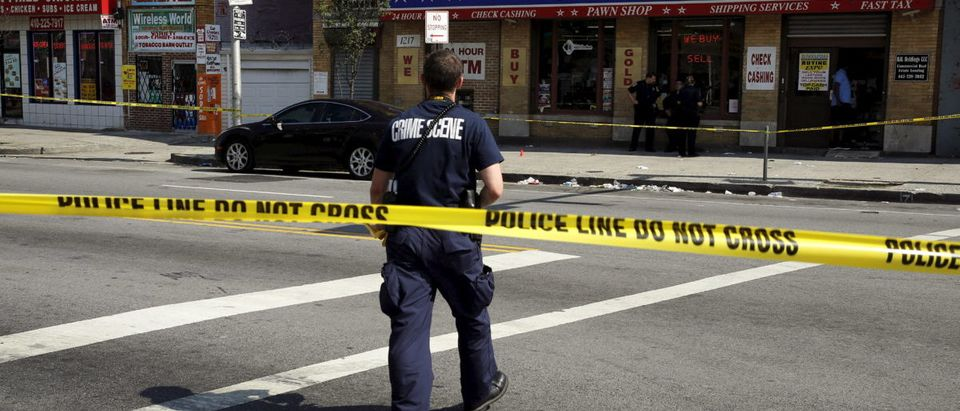 A police crime scene technician heads in to document evidence at the scene of a shooting at the intersection of West North Avenue and Druid Hill Avenue in West Baltimore, Maryland May 30, 2015. Local media have reported more than 35 murders in the city of Baltimore since the April rioting over the death of 25-year-old resident Freddie Gray and shootings continue regularly in his West Baltimore neighborhood. REUTERS/Jim Bourg