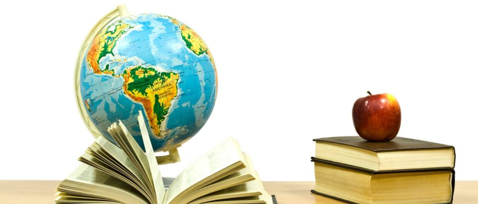 Books, an apple, and a globe sit on a student's desk in class. (Shutterstock/valzan)