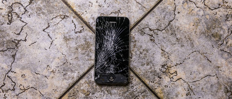 A cracked smartphone lying on the ground. [Shutterstock - Rokas Tenys]