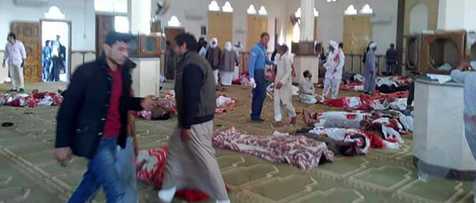Egyptians walk past bodies following a gun and bombing attack at the Rawda mosque, roughly 40 kilometres west of the North Sinai capital of El-Arish, on November 24, 2017. A bomb explosion ripped through the mosque before gunmen opened fire on the worshipers gathered for weekly Friday prayers, officials said. (Photo: STRINGER/AFP/Getty Images)
